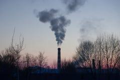 Il tubo della fabbrica fuma contro lo sfondo di un tramonto rosso Immagine Stock