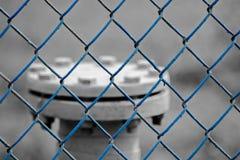 Il tubo di gas serrato dietro il recinto blu fotografia stock libera da diritti