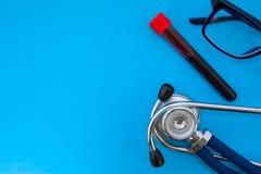 Il tubo di plastica Laboratorial con sangue per l'analisi e lo stetoscopio su fondo blu occupano la metà della foto, in secondo v immagini stock libere da diritti