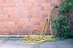Il tubo flessibile di giardino giallo si è avvolto su una casa fotografia stock libera da diritti