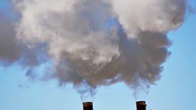 Il tubo industriale fuma il fondo del cielo blu video d archivio