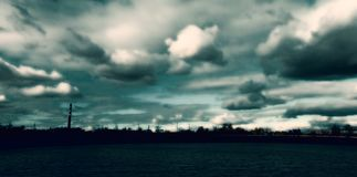 Il tubo industriale a grande schermo del paesaggio si appanna il cielo stilizzato immagine stock