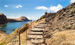 Il turista aumenta sui punti nella roccia su una costa dell'oceano, su pazzo Immagini Stock Libere da Diritti