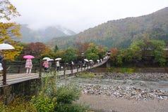 Il turista che cammina attraverso il ponte di thr a Shirakawa va villaggio durante Immagini Stock