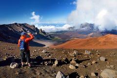Il turista che fa un'escursione in cratere del vulcano di Haleakala sulle sabbie scorrevoli trascina Bella vista del pavimento de Immagini Stock
