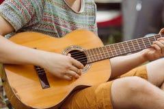 Il turista che si siede nella tenda, gioca la chitarra e canta le canzoni Fotografie Stock