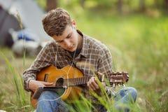 Il turista che si siede nella tenda, gioca la chitarra e canta le canzoni Immagini Stock