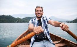 Il turista che viaggia in barca di legno tradizionale sul lago ha sanguinato, S Immagine Stock Libera da Diritti