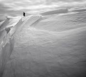 Il turista in cima alla montagna della neve Fotografia Stock