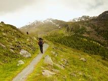 Il turista con i pali ed il grande zaino sta camminando sul percorso roccioso e sta guardando nella valle alpina Fotografie Stock Libere da Diritti