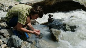 Il turista dell'uomo beve l'acqua dalle palme di una fine del fiume della montagna su archivi video