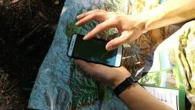 Il turista dell'uomo si siede nella foresta ed usa una mappa elettronica sul telefono, controlla l'itinerario su una mappa di car stock footage