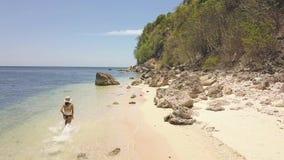 Il turista della donna in bikini sta correndo sulla spiaggia di sabbia in isola, vista posteriore archivi video