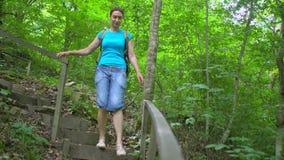 Il turista della donna cammina giù le scale dentro nel parco tropicale verde della montagna archivi video