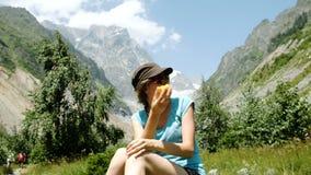 Il turista della donna si siede su una pietra e mangia una pesca in un aumento sui precedenti di bello paesaggio della montagna archivi video