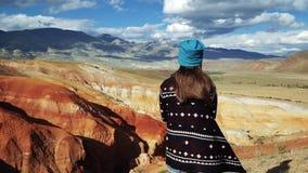 Il turista della giovane donna in cappotto del modello si siede sull'orlo di una montagna rossa C'è paesaggio scenico e cielo nuv video d archivio