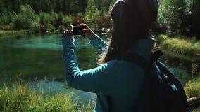 Il turista della giovane donna prende ad un'immagine su uno smartphone su un lago blu pittoresco in montagne 50 fps stock footage