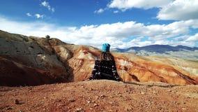 Il turista della giovane donna si siede sull'orlo di una montagna rossa C'è paesaggio scenico e cielo nuvoloso nei precedenti video d archivio