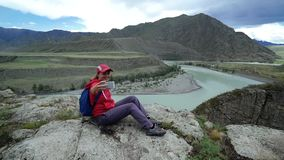 Il turista della giovane donna sta sedendosi su una pietra e sta prendendo la foto di auto sullo smartphone Bella montagna e mont stock footage