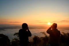 Il turista della siluetta prende a foto la bella montagna del paesaggio fotografia stock