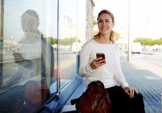 Il turista femminile allegro che per mezzo del telefono cellulare per la mappa di vista via la rete e continua la sua passeggiata Fotografia Stock