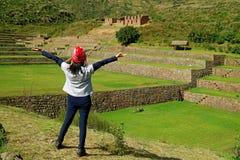 Il turista femminile che la alza armi che ritengono impressionate con l'inca ha fatto un passo rovine agricole del sito archeolog fotografie stock libere da diritti