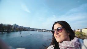 Il turista femminile elegante sorridente che fa il selfie sull'argine che gode della vacanza europea POV ha sparato archivi video