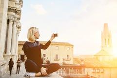 Il turista femminile splendido sta sparando il video di bello paesaggio della città sul suo telefono delle cellule Fotografia Stock