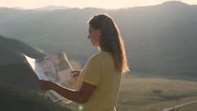 Il turista femminile sta sull'orlo di una scogliera con una mappa in sue mani e cerca un itinerario per il viaggio archivi video