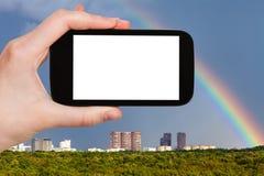 il turista fotografa l'arcobaleno sopra le case urbane Immagine Stock