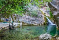 Il turista gode delle viste di piccola cascata pittoresca Fotografia Stock Libera da Diritti