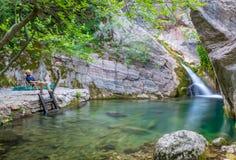 Il turista gode delle viste di piccola cascata pittoresca Immagini Stock Libere da Diritti