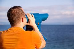 Il turista guarda il bello ambiente naturale in telescopio sulla spiaggia/sul panorama e sulla vista del mare e del cielo Fotografie Stock