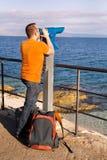 Il turista guarda il bello ambiente naturale in telescopio sulla spiaggia/sul panorama e sulla vista del mare e del cielo Immagini Stock Libere da Diritti
