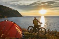 Il turista guida una bici con le ampie ruote lungo la riva del lago Baikal immagini stock