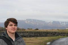 Il turista ha invecchiato 20 - 25 pose davanti ad una regione montagnosa a Reykjavik Islanda fotografia stock libera da diritti