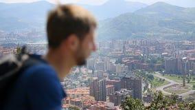 Il turista maschio che esamina la grande città, coprente osserva con la mano contro il sole, viaggio video d archivio