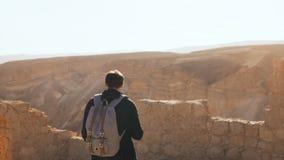 Il turista maschio fotografa il paesaggio stupefacente della montagna Il giovane con lo zaino prende le foto Libertà Masada Israe video d archivio