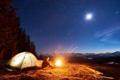 Il turista maschio ha un resto nel suo campo alla notte sotto bello cielo notturno in pieno delle stelle e della luna Fotografia Stock