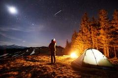 Il turista maschio ha un resto nel suo campo alla notte sotto bello cielo notturno in pieno delle stelle e della luna Immagine Stock Libera da Diritti