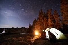 Il turista maschio ha un resto nel suo campo vicino alla foresta alla notte sotto bello cielo notturno in pieno delle stelle Fotografie Stock Libere da Diritti