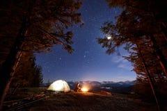 Il turista maschio ha un resto nel suo campo vicino alla foresta alla notte sotto bello cielo notturno in pieno delle stelle e de Fotografia Stock Libera da Diritti