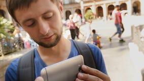 Il turista maschio si è concentrato sulla presa del video con il telefono cellulare al quadrato, primo piano stock footage