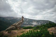Il turista maschio si siede su un'alta roccia sopra la parte anteriore verde conifera Fotografia Stock
