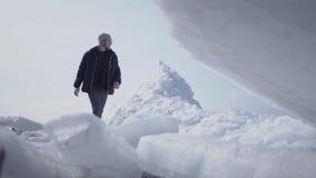 Il turista maschio solo sui precedenti che cammina sul ghiacciaio Punto di vista di stupore di un polo Sud del nord o nevoso Il g video d archivio