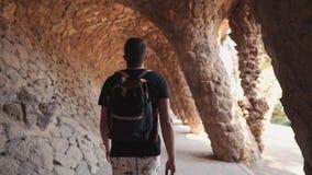 Il turista maschio sta camminando da solo in vicolo della grotta artificiale con le colonne in parco archivi video