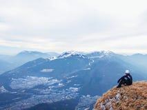 Il turista nel nero si siede sul picco della collina Turista stanco sul picco del picco congelato dell'erba della collina in alpi Fotografie Stock Libere da Diritti