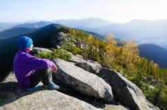 Il turista nelle montagne contempla la bellezza di autunno di natur Fotografia Stock