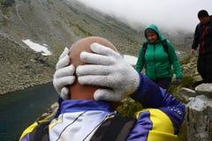 Il turista riscalda le sue orecchie dopo il raffreddamento improvviso nelle montagne immagini stock libere da diritti