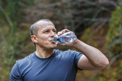 il turista si siede e beve l'acqua Fotografia Stock